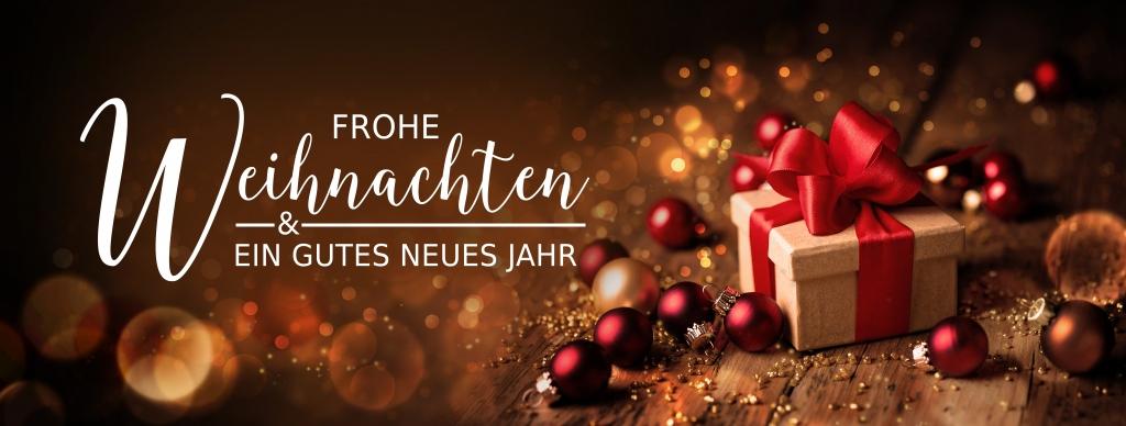 Weihnachtskarte - Grußkarte zu Weihnachten - Frohe Weihnachten und ein gutes neues Jahr - Banner, Panorama, Header - Geschenk mit Christbaumkugeln auf Holz